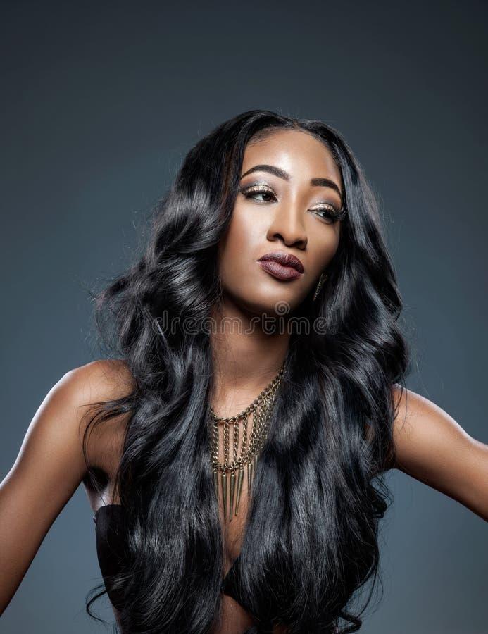 Чернокожая женщина с длинными роскошными сияющими волосами стоковое изображение rf