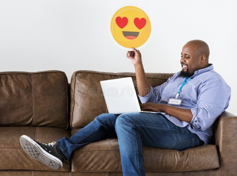 Чернокожий человек работая на компьтер-книжке сидя на кресле стоковые фотографии rf