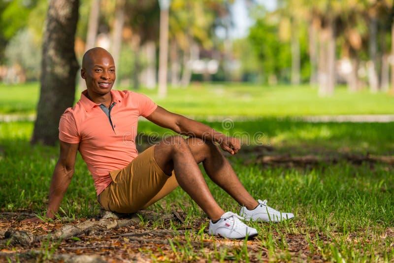 Чернокожий человек фото молодой сидя в парке Человек нося случайную розовую рубашку и шорты поло стоковая фотография
