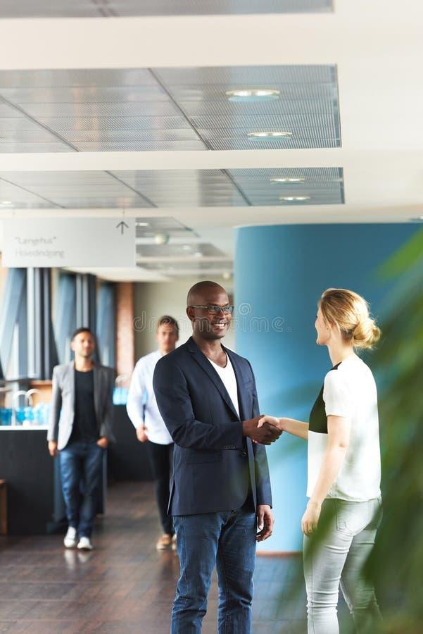 Чернокожий человек и белая женщина тряся руки в офисе стоковая фотография