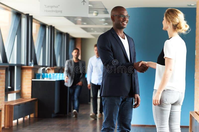 Чернокожий человек и белая женщина усмехаясь и тряся руки стоковое фото