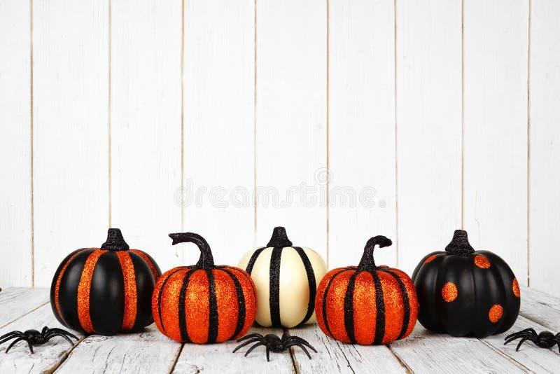 Чернота и оранжевые glittery тыквы хеллоуина против белой древесины стоковые изображения