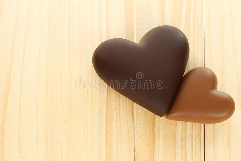 Чернота и сердца молочного шоколада на деревянной предпосылке стоковые изображения rf