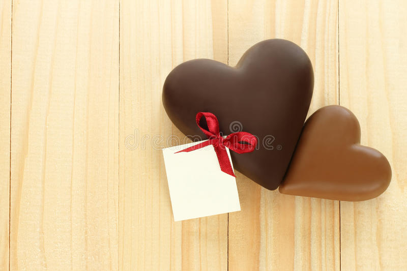 Чернота и сердца молочного шоколада на деревянной предпосылке стоковые фотографии rf