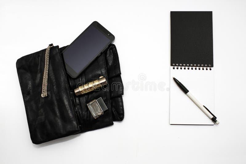 Черно-белая концепция Муфта сумки современной дамы дела с мобильным телефоном, кредитными карточками, наличными деньгами, тетрадь стоковое фото