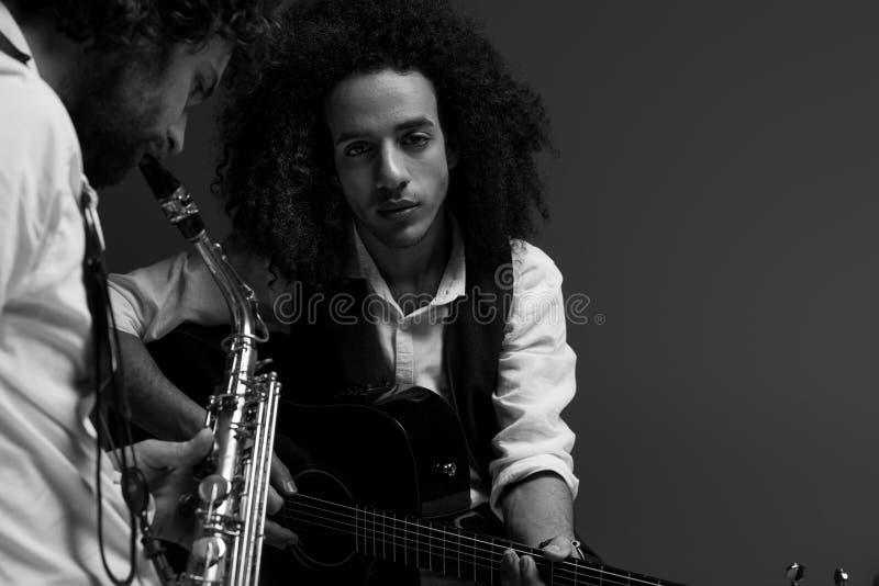 черно-белая съемка дуэта музыкантов играя саксофон и акустическую гитару стоковое изображение rf