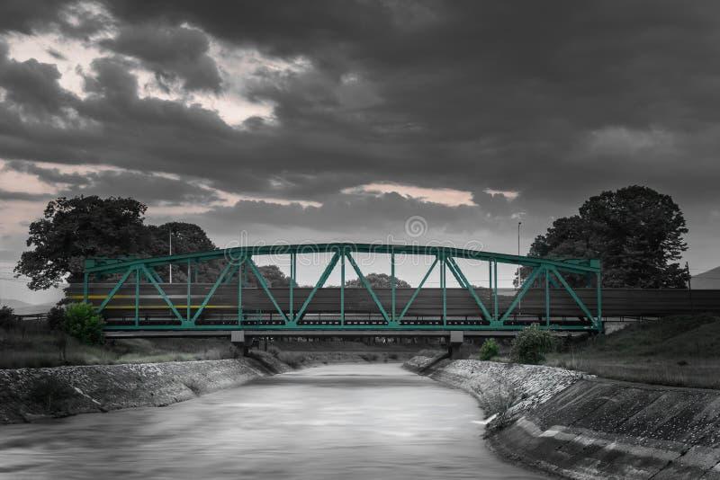 Черно-белое движение запачкало поезд пропуская над металлическим железнодорожным мостом на заходе солнца стоковые фотографии rf