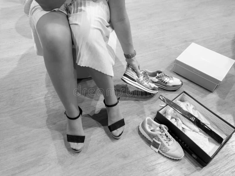 Черно-белое изображение молодой женщины выбирая какие ботинки для покупки Девушка пробуя на новых ботинках в магазине стоковые фотографии rf