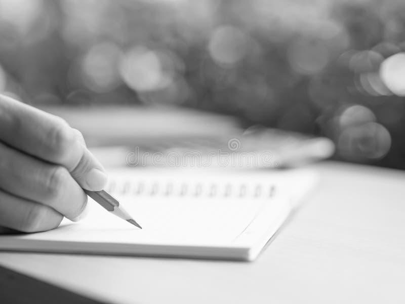 Черно-белое сочинительство руки женщины с красным карандашем, шиной стоковая фотография rf