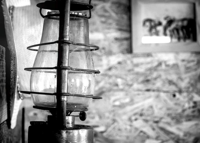 Черно-белое фото, винтажная комната, старая лампа и шляпа ковбойской шляпы на стене, на предпосылке изображение лошадей стоковая фотография