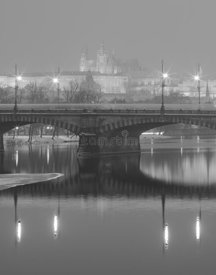Черно-белое фото зимы моста через реку Влтавы отражая на поверхности воды и замке Праги стоковое фото rf