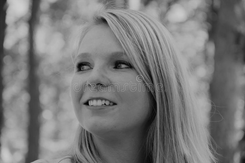 Черно-белое фото профиля усмехаясь стороны ` s женщины стоковое фото rf