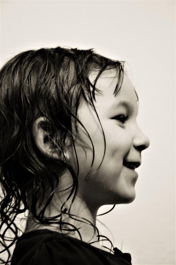 Черно-белое portait счастливого усмехаясь ребенка стоя в профиле стоковое фото rf