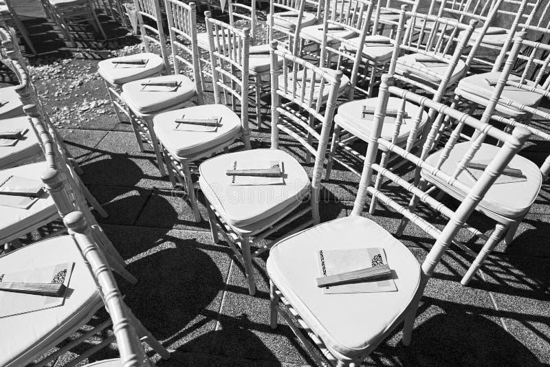 Черно-белые стулья свадьбы с конусом лепестков розы и сувенира - взгляд сверху стоковые фото
