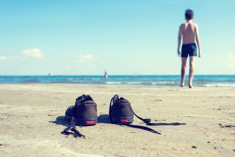 Черно-белые тапки на песке на предпосылке моря и мальчика Лето и концепция перемещения стоковое изображение rf