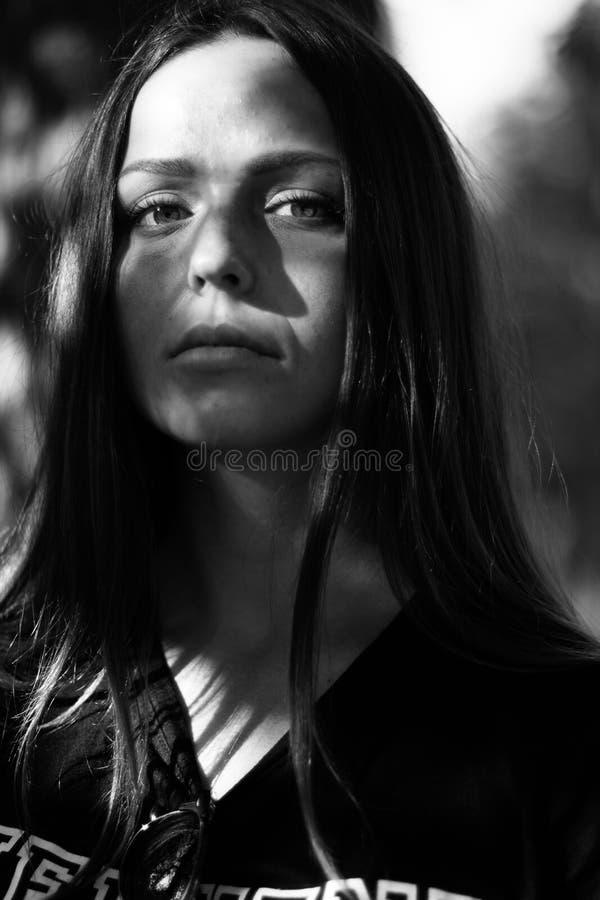 Черно-белый портрет красивой девушки с длинными волосами в черной футболке смотря сразу на камере r стоковое фото rf