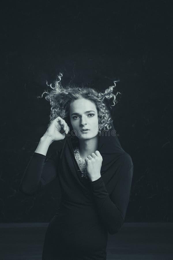 Черно-белый портрет Красивый андрогинный молодой человек в изображении женщины страстно представляя против темной предпосылки стоковое изображение