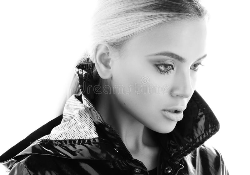 Черно-белый портрет красоты красивой молодой женщины в черном лоснистом пальто стоковое фото rf