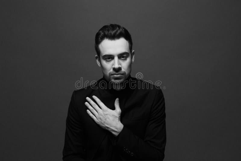 Черно-белый портрет молодого красивого человека в костюме, вручает квартиру на комоде стоковое изображение