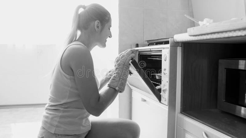 Черно-белый портрет молодой усмехаясь женщины печь вкусные сладкие печенья в печи дома на кухне стоковое изображение