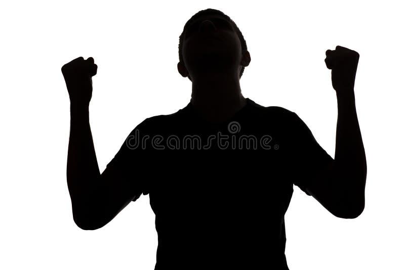Черно-белый силуэт sporty молодого мужчины победоносно поднимая его оружия вверх изолированный против белой предпосылки, идеи кон стоковое изображение rf