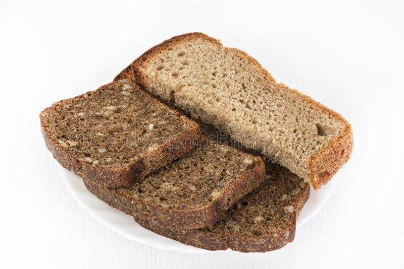 Черно-белый хлеб на белой плите на белизне изолировал предпосылку стоковое фото