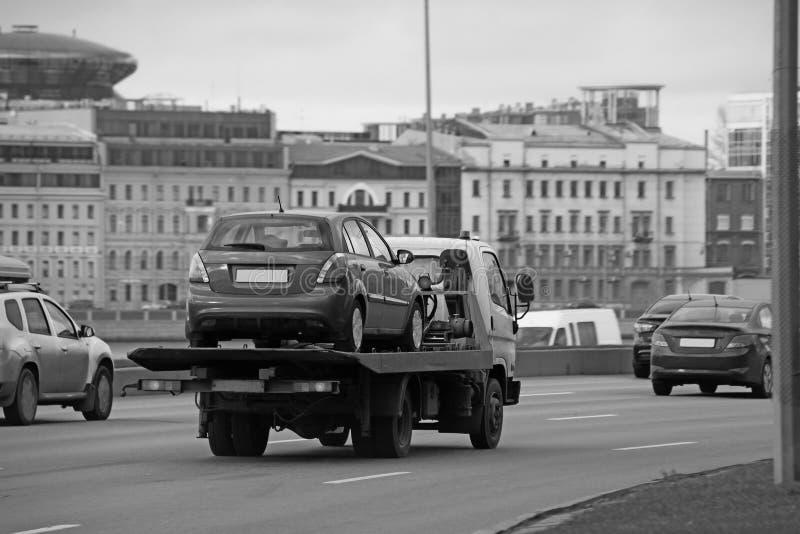 Черно-белый эвакуатор нося автомобиль на улице города стоковые фото