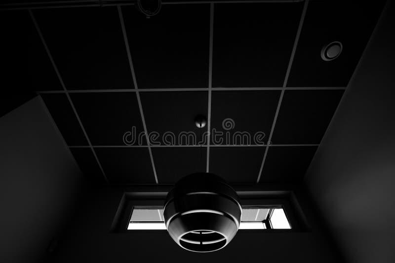 Черно-белая съемка футуристической лампы в потолке коридора современного администраривного администраривн офиса стоковое фото rf