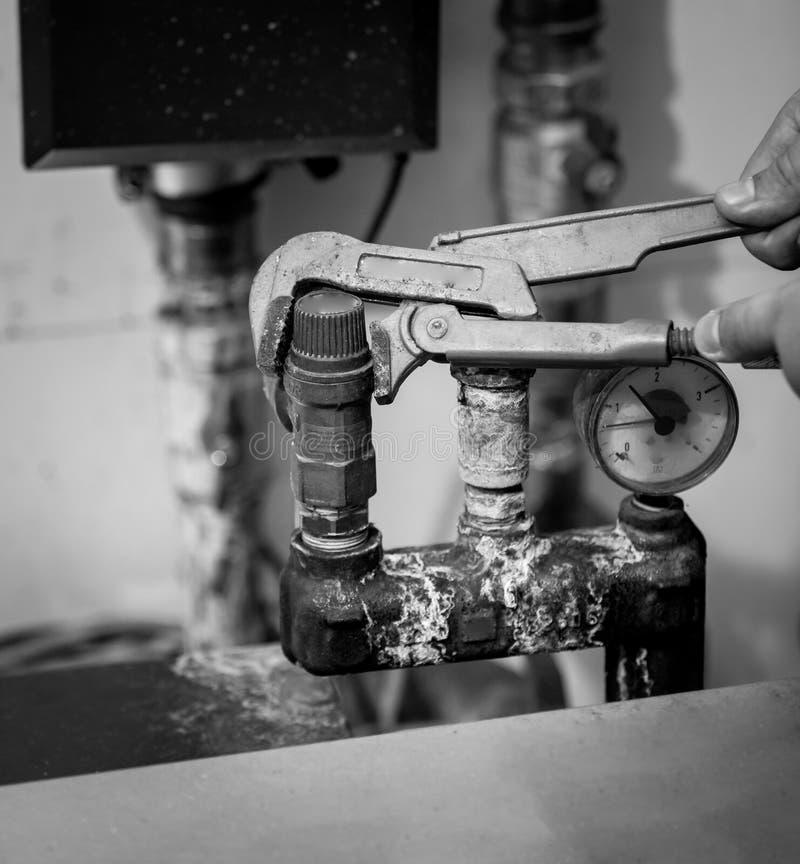 Черно-белая съемка человека ремонтируя систему отопления стоковые фото