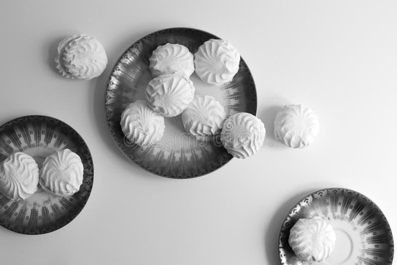 Черно-белое изображение латышских marshmallovs - zefiri на плитах фарфора на белой предпосылке стоковая фотография