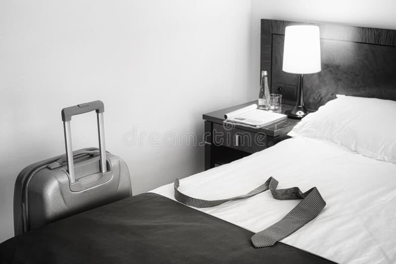 Черно-белое изображение связи на кровати и чемодана в пустой ho стоковая фотография