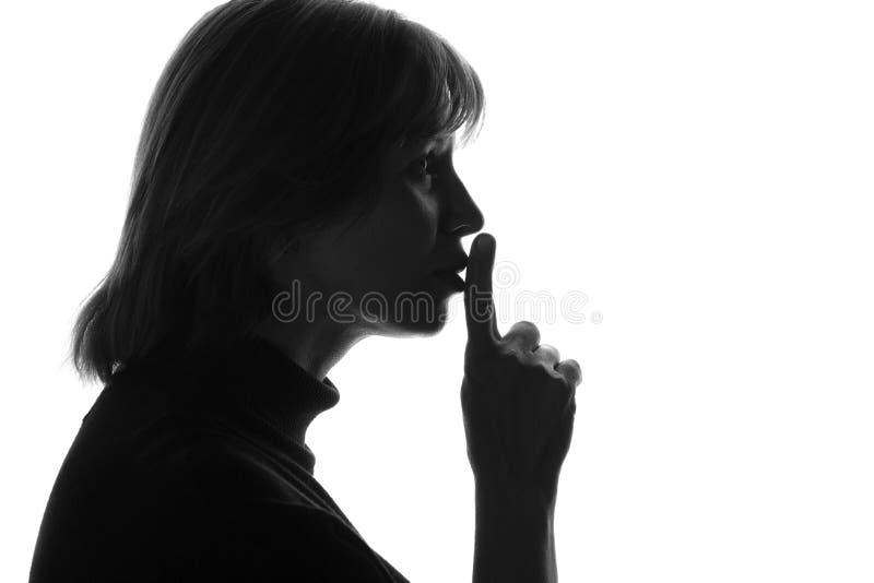Черно-белое фото женщины которая отрезала его указательный палец к его принуждать губ молчаливый стоковое изображение