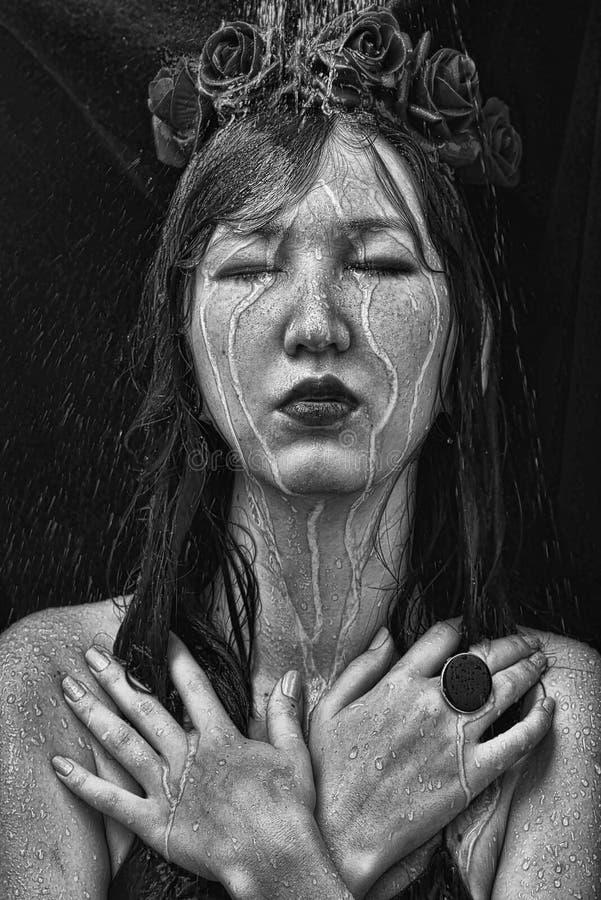Черно-белое фото женщины с розами на ее голове, оружиями пересекло под струи воды стоковая фотография rf