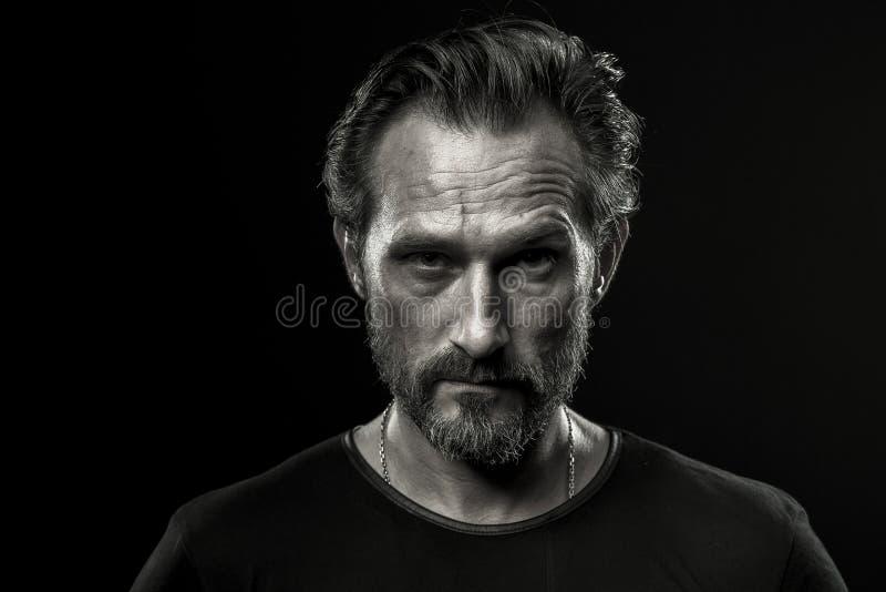 Черно-белое фото среднего постаретого человека показывая строгую эмоцию стоковое фото rf