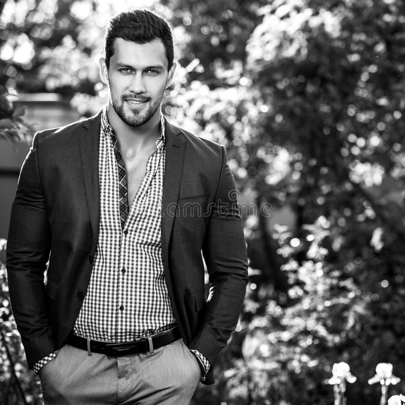 Черно-белый внешний портрет элегантного красивого человека в классической куртки предпосылке природы снова стоковые фотографии rf