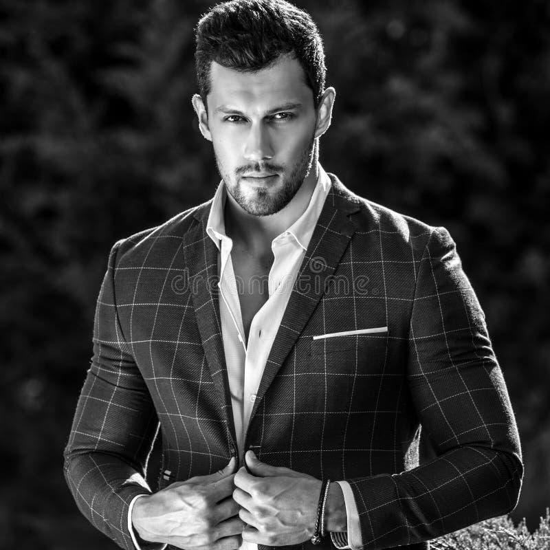 Черно-белый внешний портрет элегантного красивого человека в классической куртки предпосылке природы снова стоковое фото rf