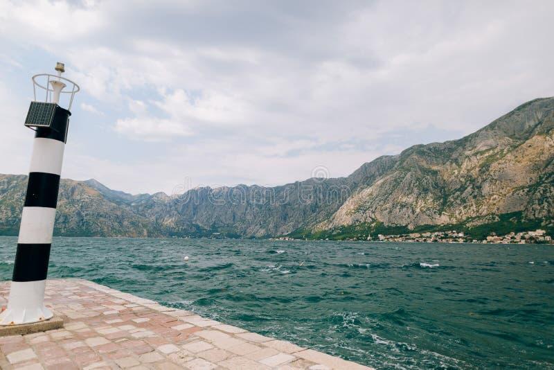 Черно-белый маяк в море Prcanj, залив Kotor, Monten стоковая фотография