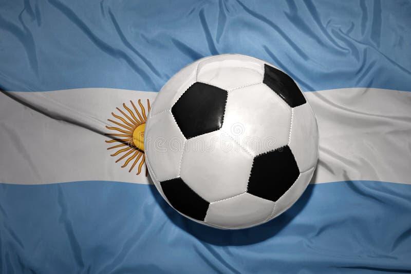 Черно-белый шарик футбола на национальном флаге Аргентины стоковые фото