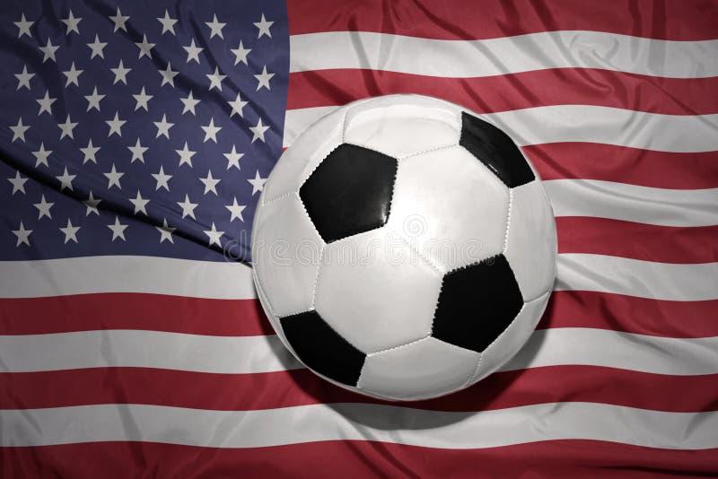 Черно-белый шарик футбола на национальном флаге Соединенных Штатов Америки стоковое изображение rf
