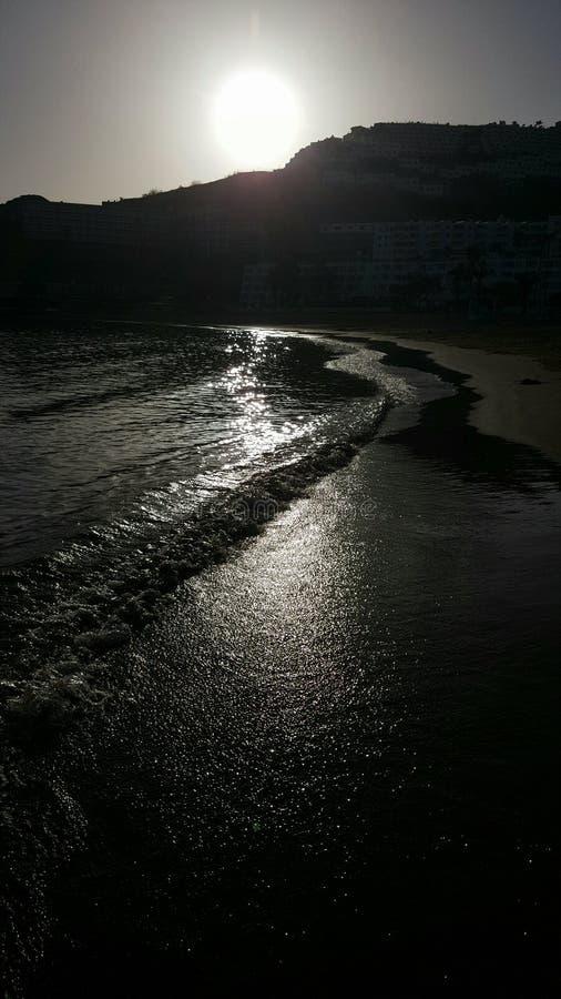 Черные волны пляжа прилива океана на заходе солнца отражают солнце стоковая фотография rf