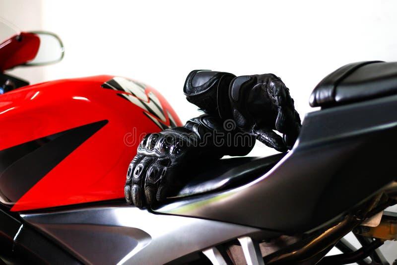 Черные кожаные перчатки мотоцикла лежат на красном велосипеде спорт стоковые фото