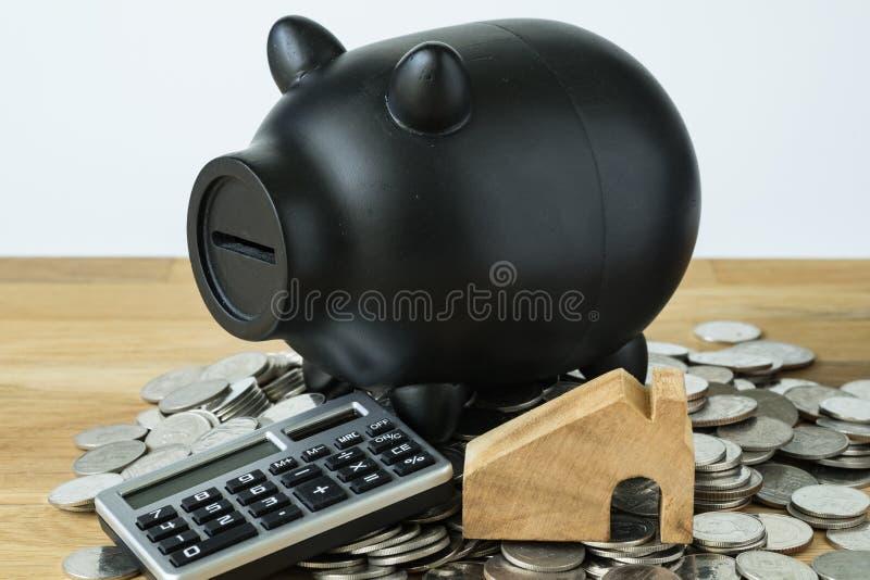 Черные копилка с калькулятором и монетками дальше как сбережения или finan стоковое фото
