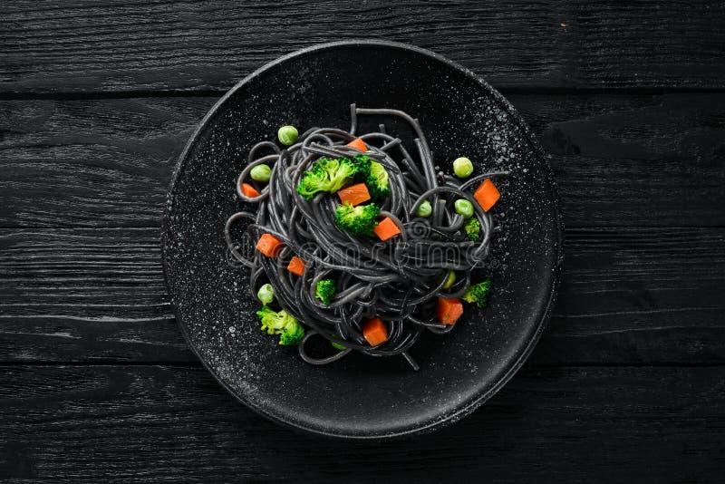 Черные макаронные изделия с овощами на черной плите стоковая фотография rf