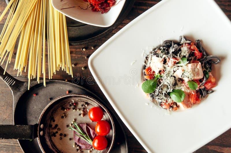 Черные макаронные изделия fettuccine с salmon составом рыб и томатов на темной деревянной предпосылке стоковая фотография