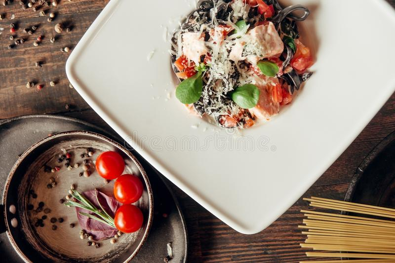 Черные макаронные изделия fettuccine с salmon составом рыб и томатов на темной деревянной предпосылке стоковое фото rf