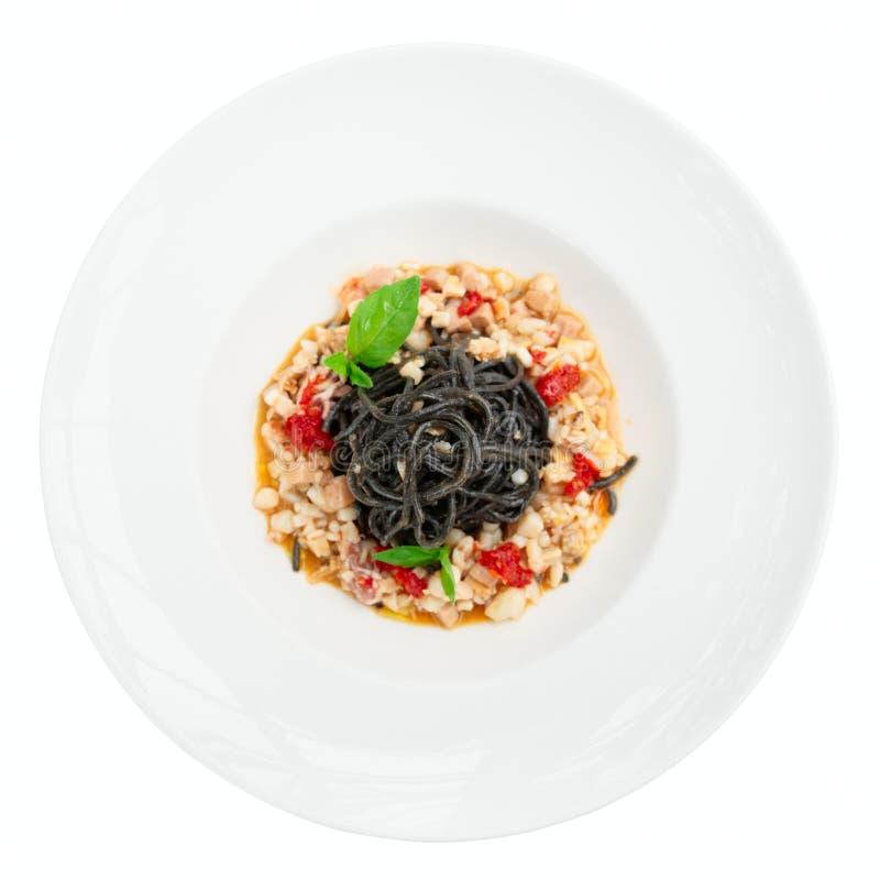 Черные макаронные изделия чернил кальмара с морепродуктами в изолированной плите, стоковое изображение