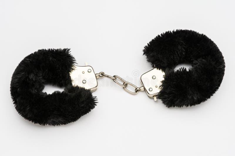 Черные меховые наручники на белой предпосылке стоковое фото rf