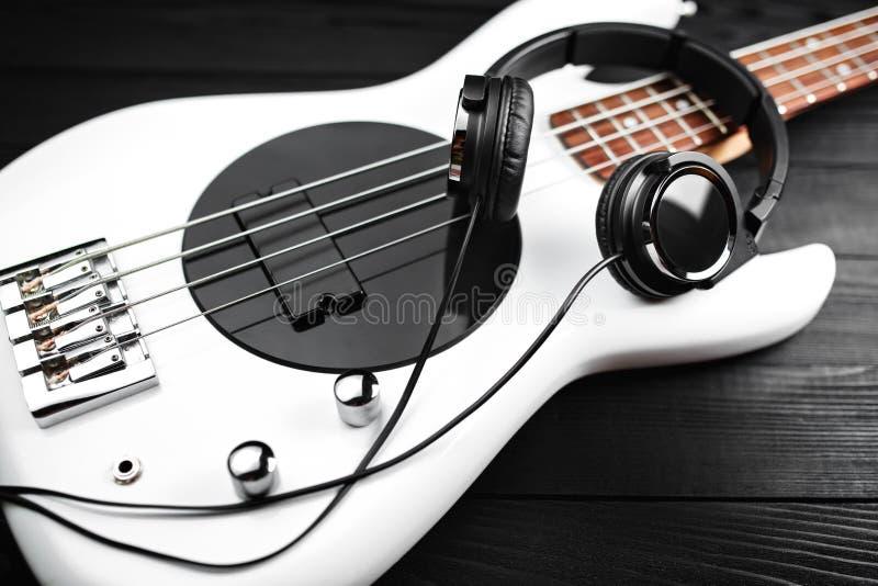 Черные наушники и белая басовая гитара на черной деревянной предпосылке стоковое фото