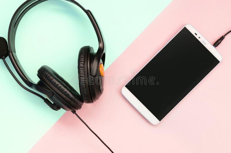 Черные наушники и лож смартфона на красочной пастельной розовой предпосылке стоковые фотографии rf