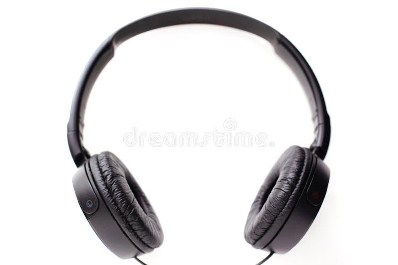 Черные наушники на белых наушниках предпосылки, левых и правых с оправой рамки для слушать громкую музыку стоковые фото